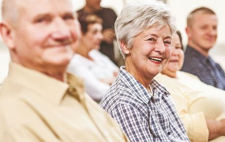 older woman with gray hair smiling next to man smiling